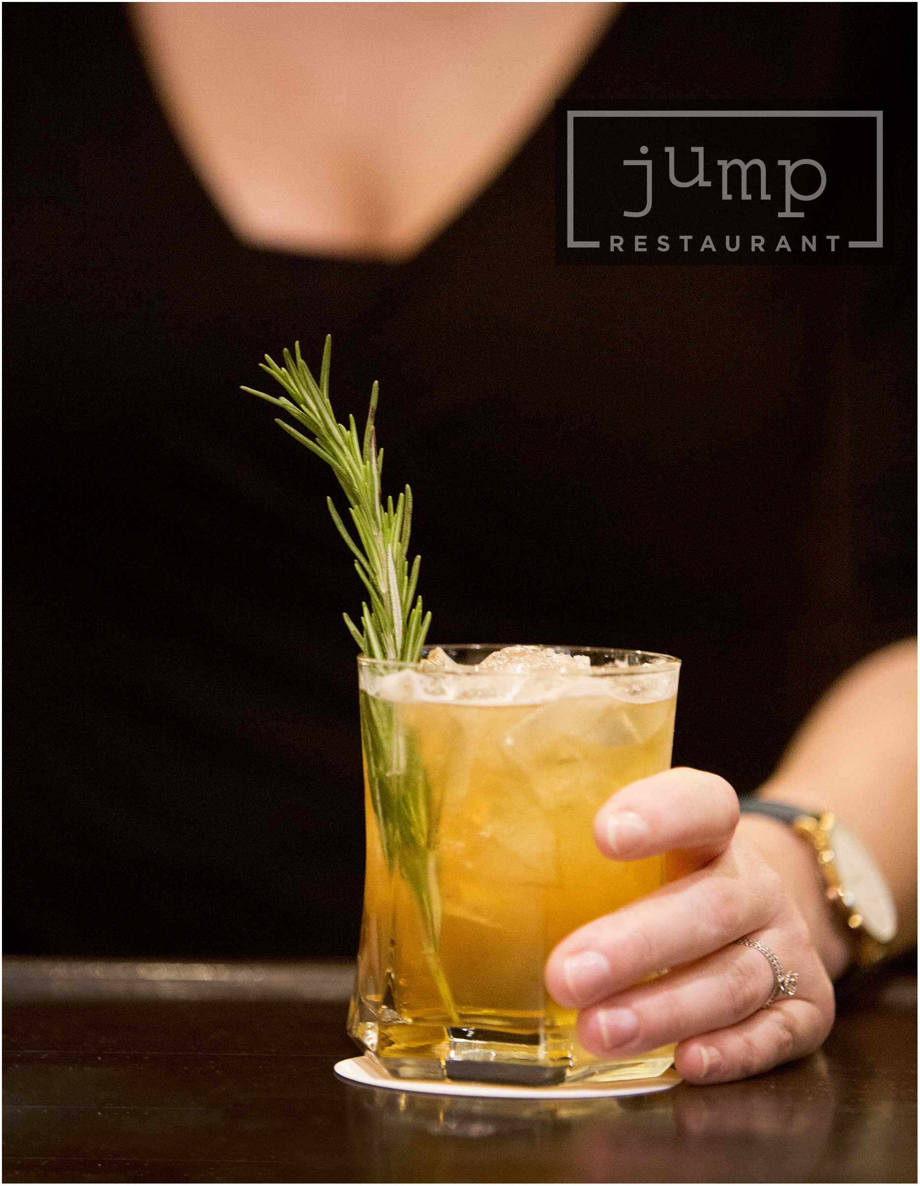 Person holding cocktail with rosemary sprig