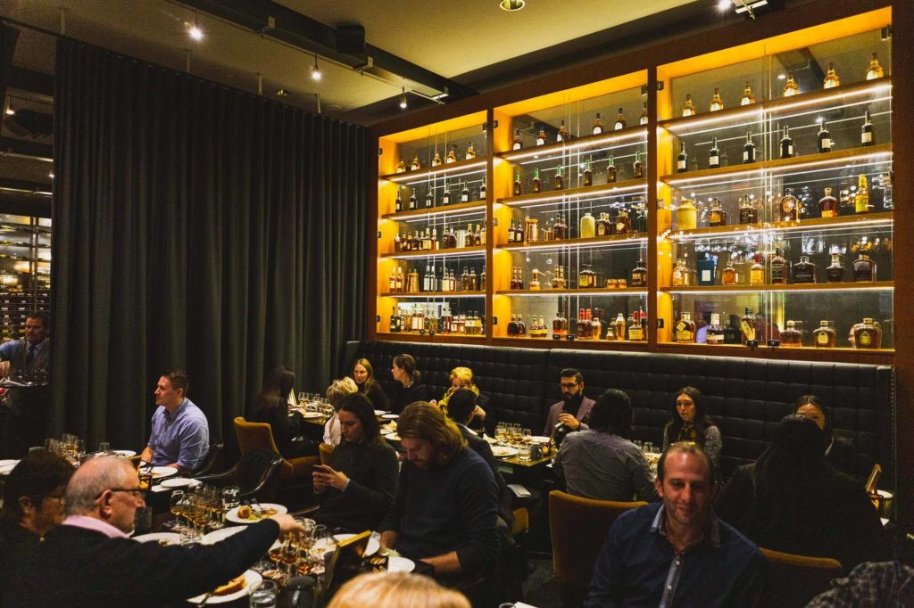 Full dining room with guests in front of whisky wall