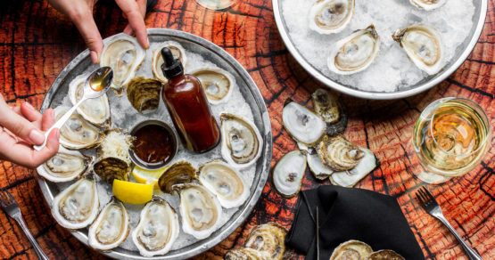 A table setup with oysters and wine glasses