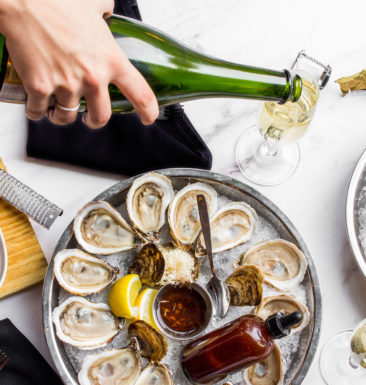 Hand pouring wine in a champagne flute, next to a table with two dishes of oysters