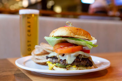 Bannock's burger next to a Lost Craft Beer on a wooden table