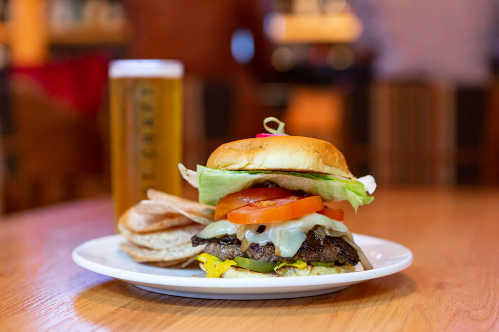 Bannock's burger special on a wooden table with a beer behind it