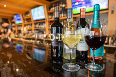 4 bottles of wine lined up on the Bannock bar with two glasses in front of them. One is filled with red wine, the other is filled with white.