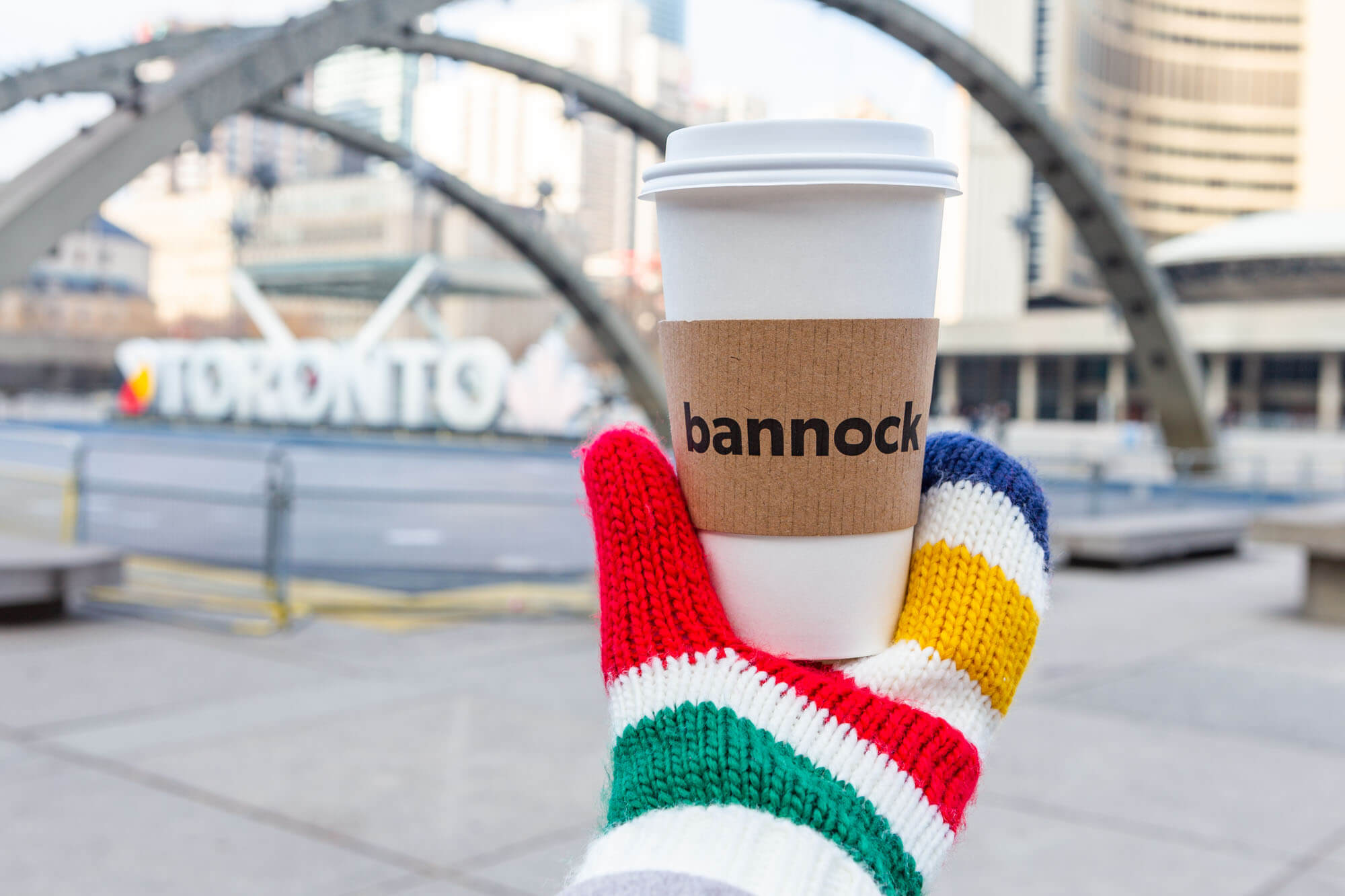 HBC mitten holding a Bannock coffee cup in front of Nathan Phillips' Square
