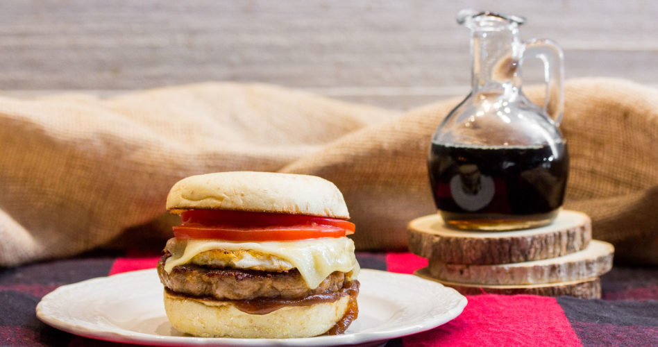 Maple-Glazed Pork breakfast sandwich on plaid tablecloth with a glass jar of maple syrup in the background