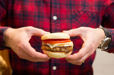 A man in a plaid shirt holding the maple-glazed pork breakfast sandwich against his chest with two hands.