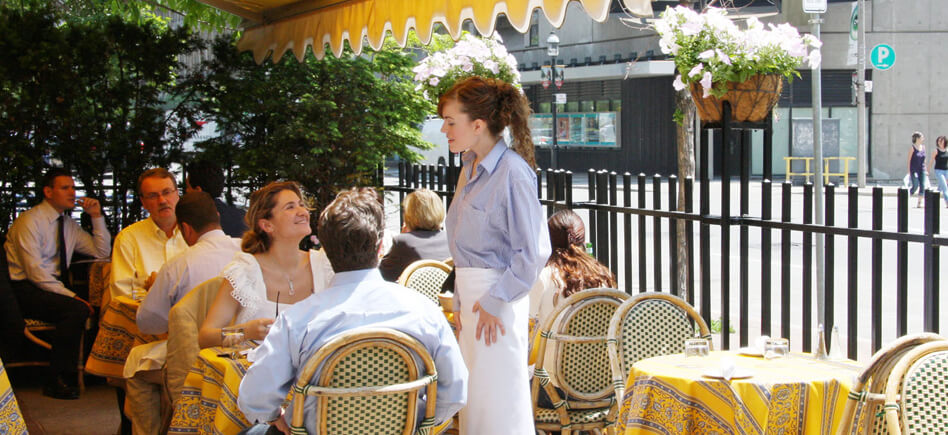 Guests interacting with a server on the patio at Biff's Bistro.
