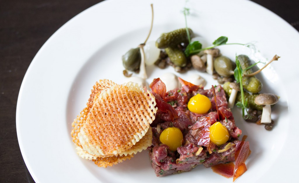 Steak tartare served with crisps and capers on a white plate.