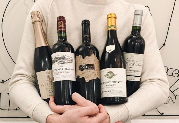 A server in a white sweater holding five bottles of wine