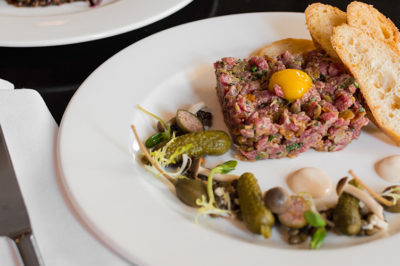 Biff's Steak Tartare served with bread and garnished with pickles and capers