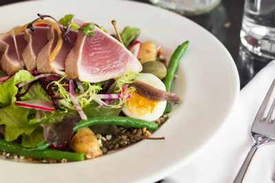 Tuna Nicoise salad placed beside a white napkin and fork