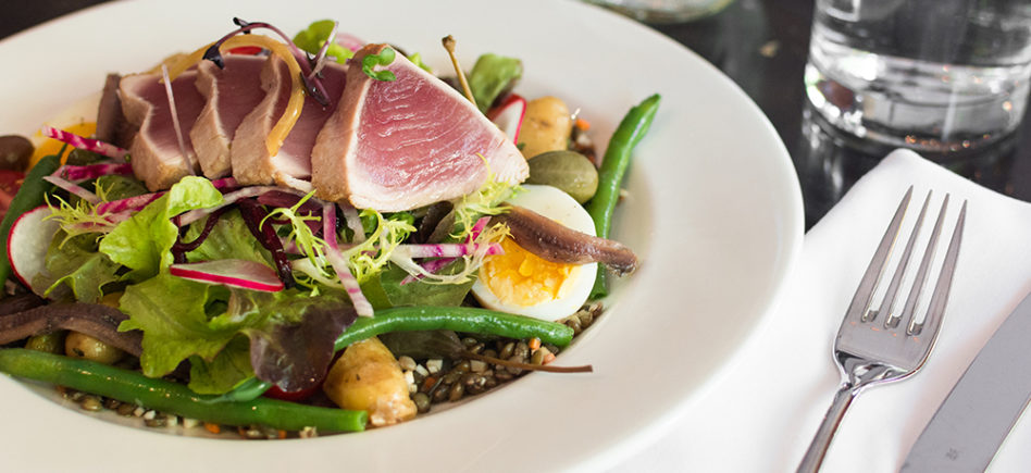 Tuna Nicoise salad placed beside a white napkin and fork
