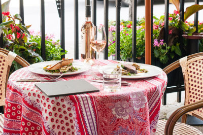 Table on Biff's Bistro's patio with two entrées and a bottle of rosé place on it