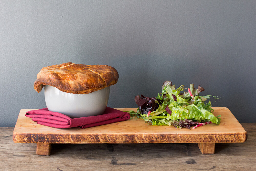 Chicken pot pie and mixed greens on a wooden board in front of a grey wall