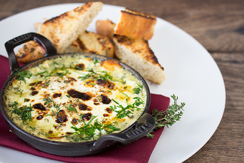Coddled eggs florentine served with bread on a white plate with a red napkin