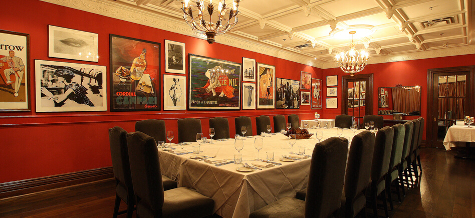 Private dining room at Biff's Bistro with red walls and a large dining table set with wine glasses.