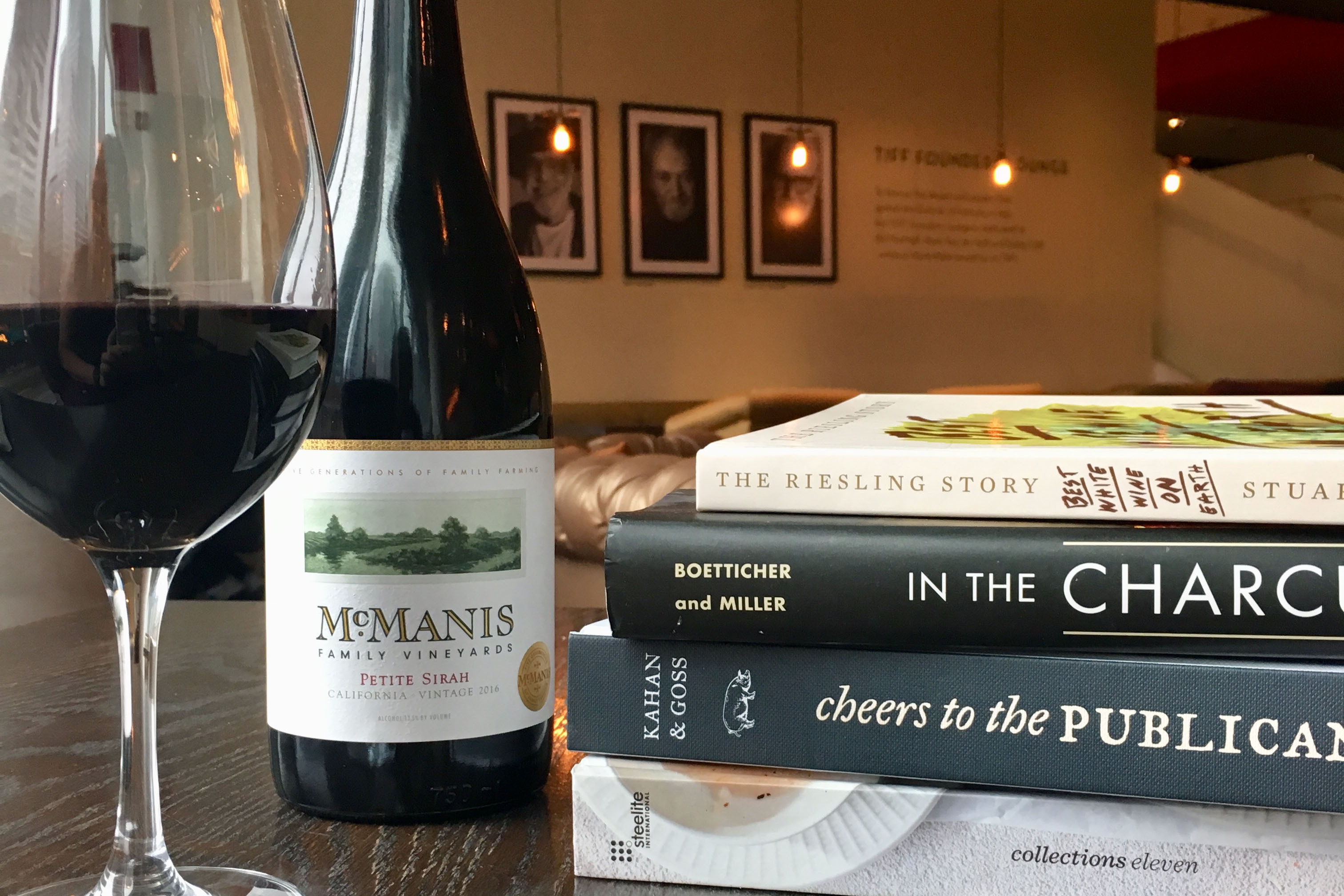 Wine Glass and Bottle Beside Books on Wood Table