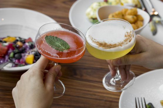 One red cocktail and one yellow cocktail clinking glasses and toasting in front of brunch dishes on wooden table