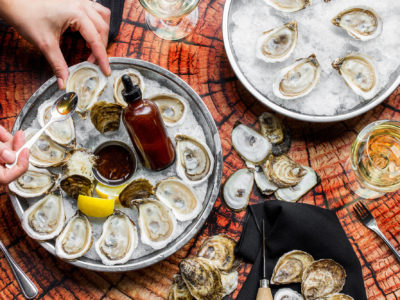 platter of oysters and garnishes on a wooden table