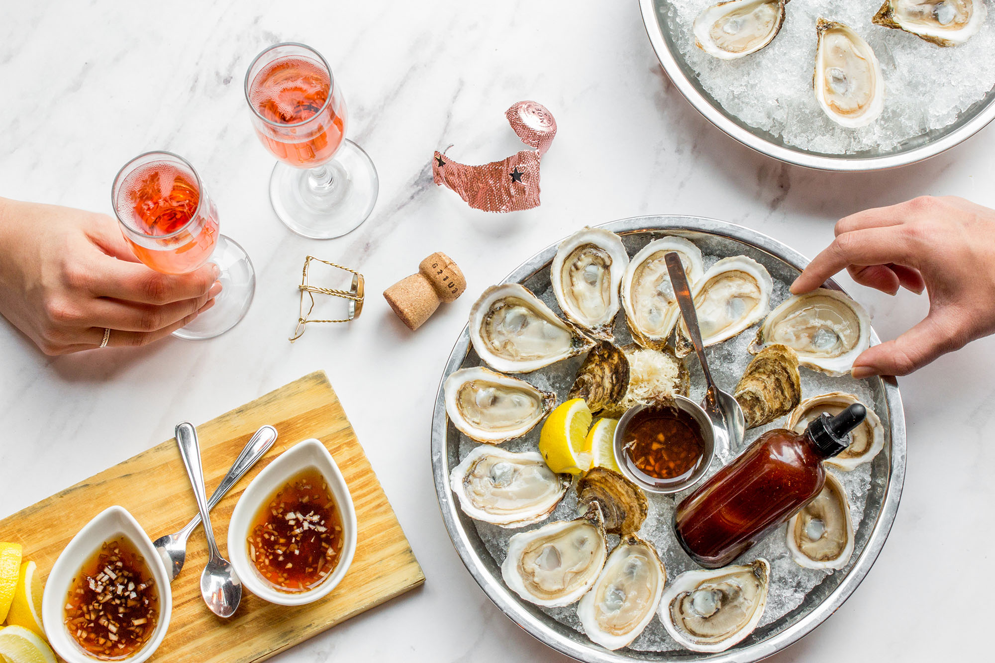 two people sharing a platter of oysters and two glasses of rose wine