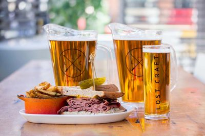 Two pitchers and a beer next to a dish on the patio