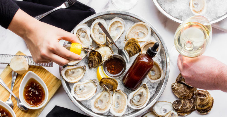 A tablescape with oysters and wine, with one hand grabbing an oyster from the tray.