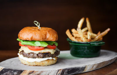 Canoe Game Day Burger sitting on a wooden block with a side of fries