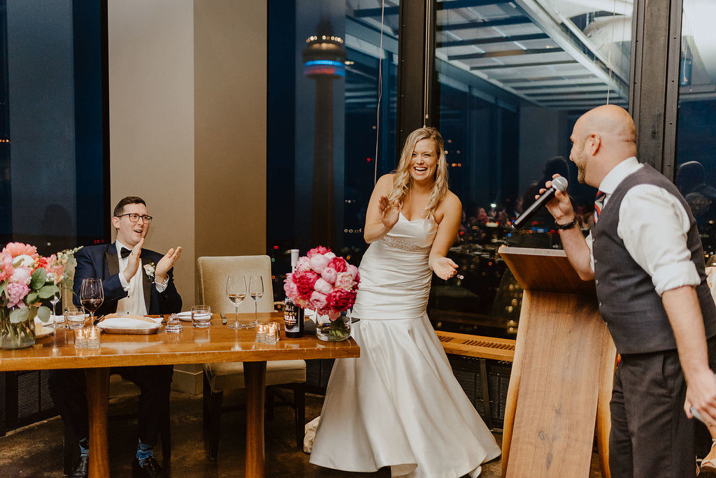 Bride and groom laughing as a groomsman makes a speech at their wedding reception at Canoe.