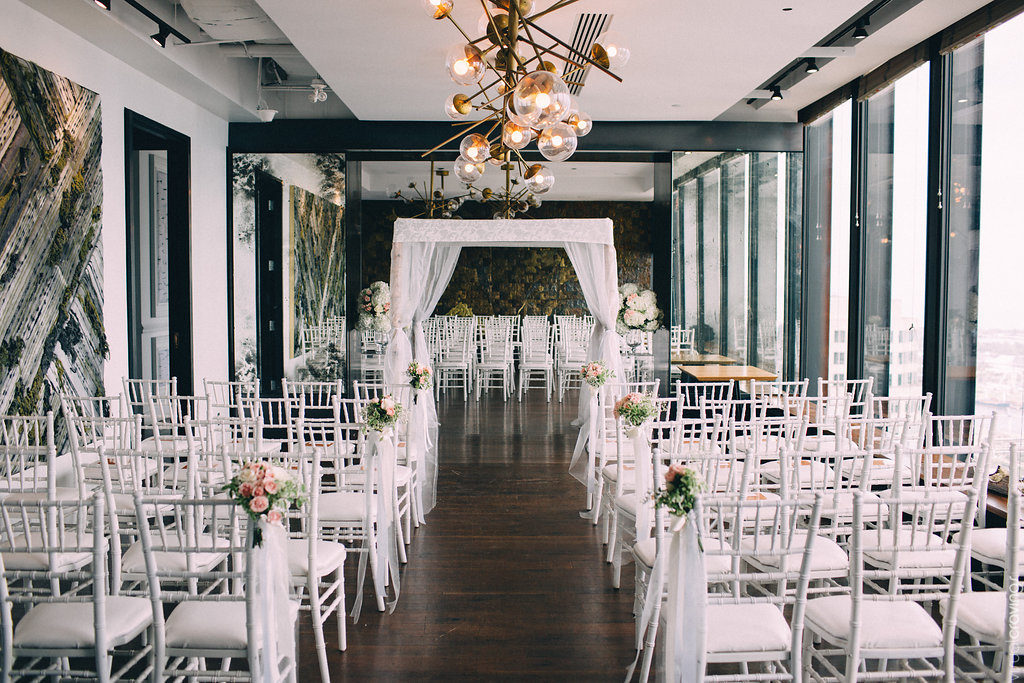 Canoe private dining rooms set for a wedding ceremony with white chairs, flowers and a chuppah.