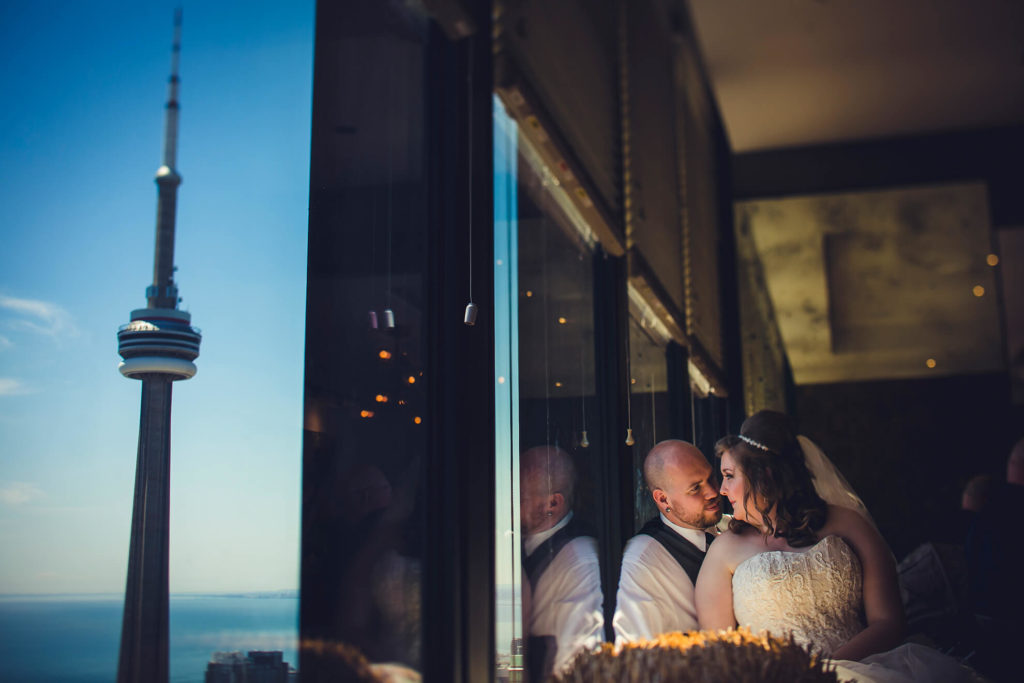 Bride and groom posing by the window at Canoe with the CN Tower in the background.