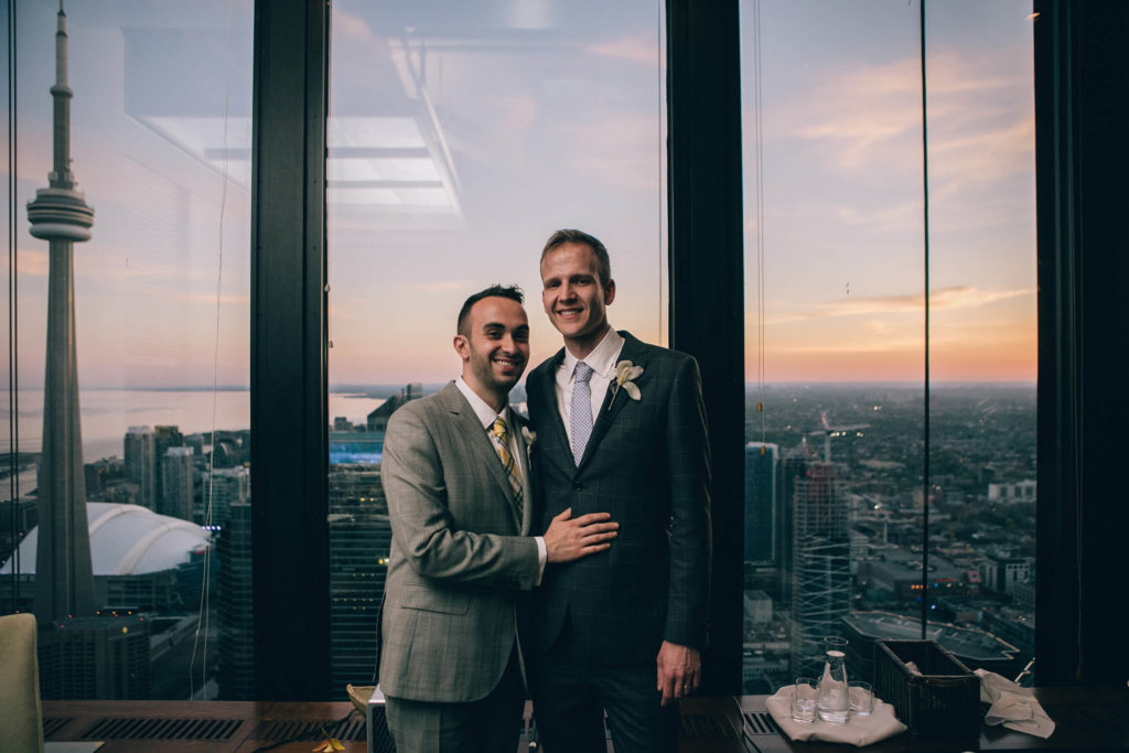 Groom and groom posing in front of the windows, overlooking the city at Canoe.
