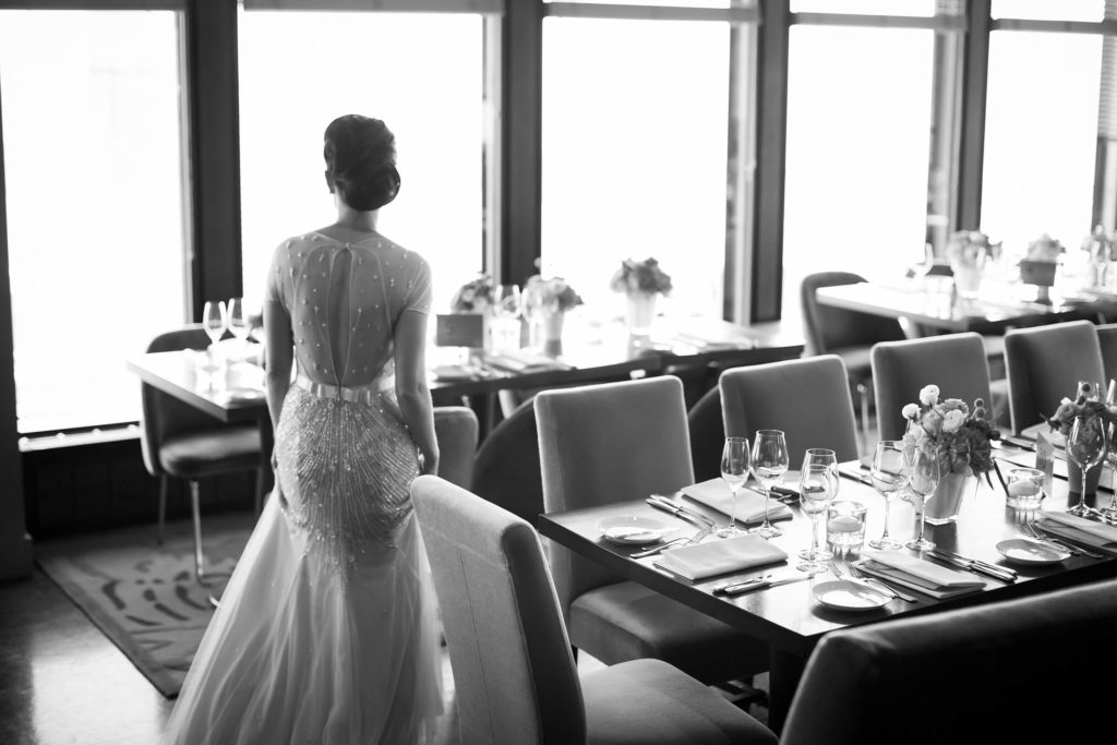 Bride in a beaded gown looking out the window of the dining room at Canoe.