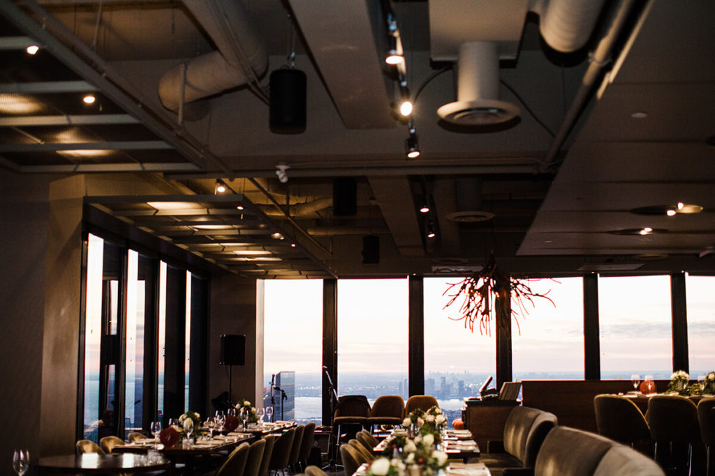 Canoe dining room dimly lit and set for a wedding reception in downtown Toronto.