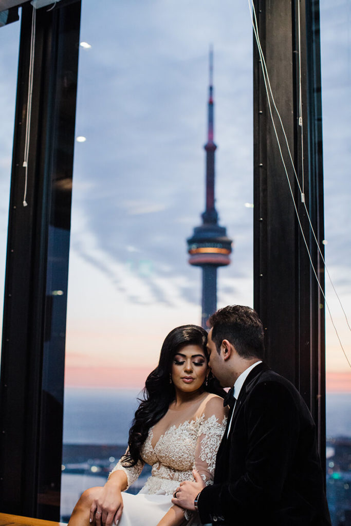 Bride and groom posting in Canoe restaurant with the CN Tower in the background.