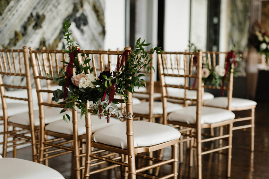 Gold chairs with floral arrangements set for a wedding ceremony in the Canoe private dining room.