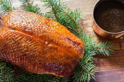 Roast duck on top of pine on wooden board with ramekin of jus