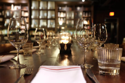Long table set with wine glasses at Sub Rosa in Calgary