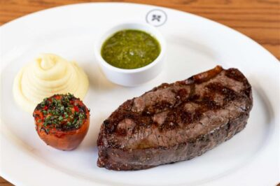 Striploin steak dinner with grilled tomato, mashed potatoes and chimichurri sauce