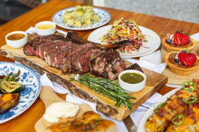 Table with sliced Tomahawk steak, sides and individual pecan tarts from Father's Day kit