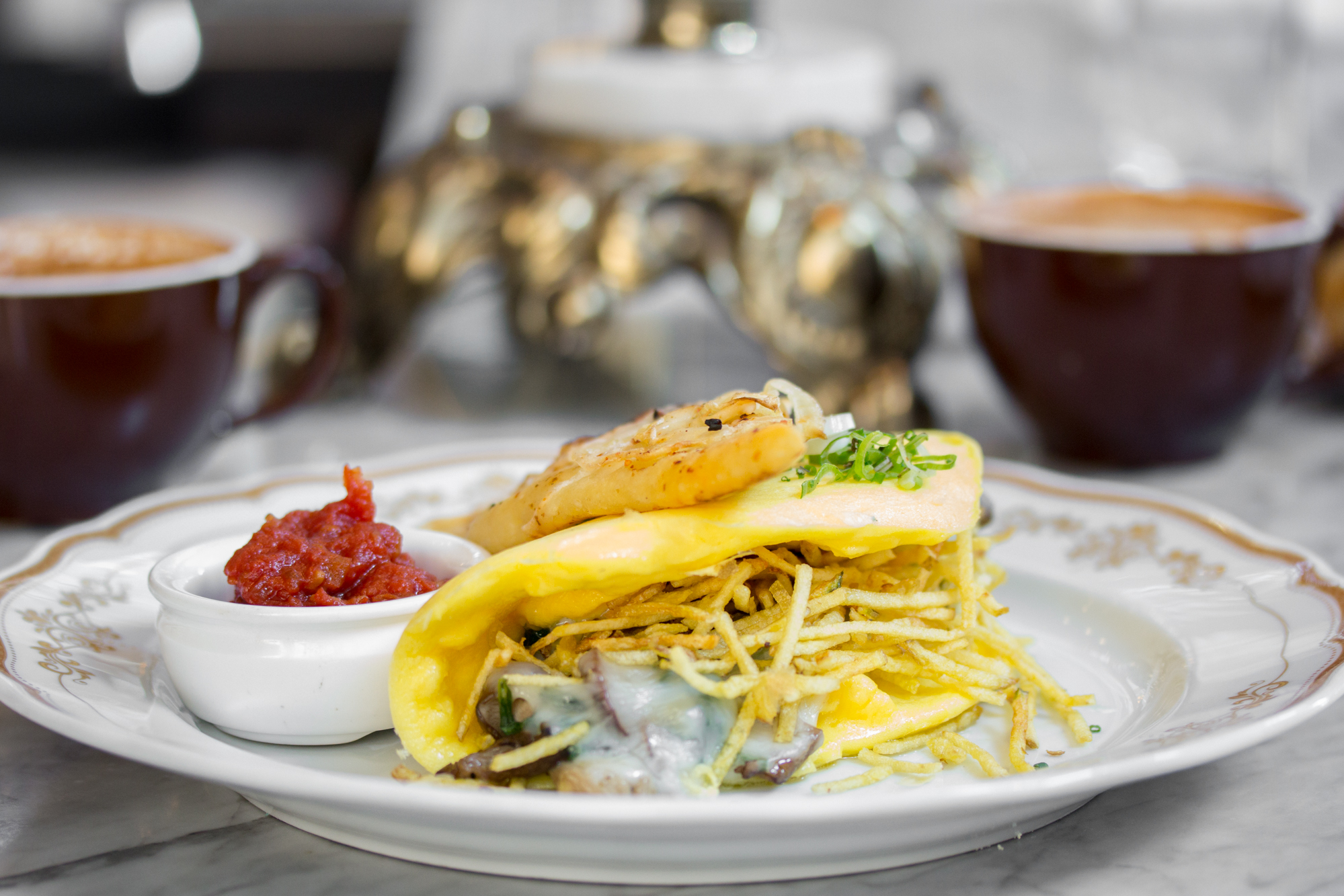 Mushroom omelette with shoestring potatoes on white plate on marble countertop