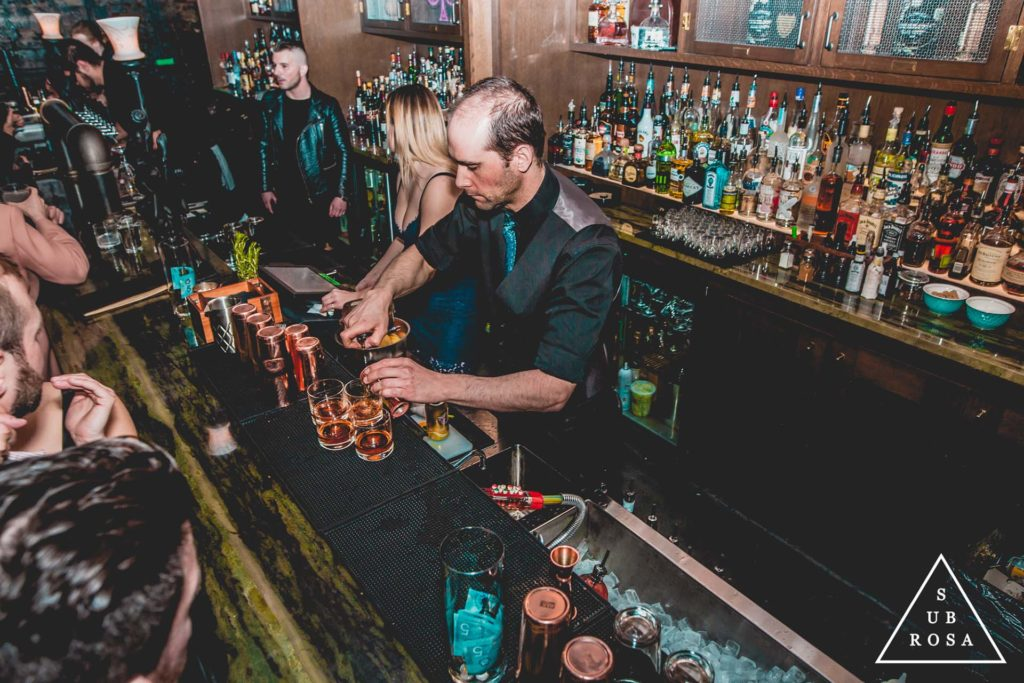 bartenders mixing craft cocktails behind the bar of an underground lounge