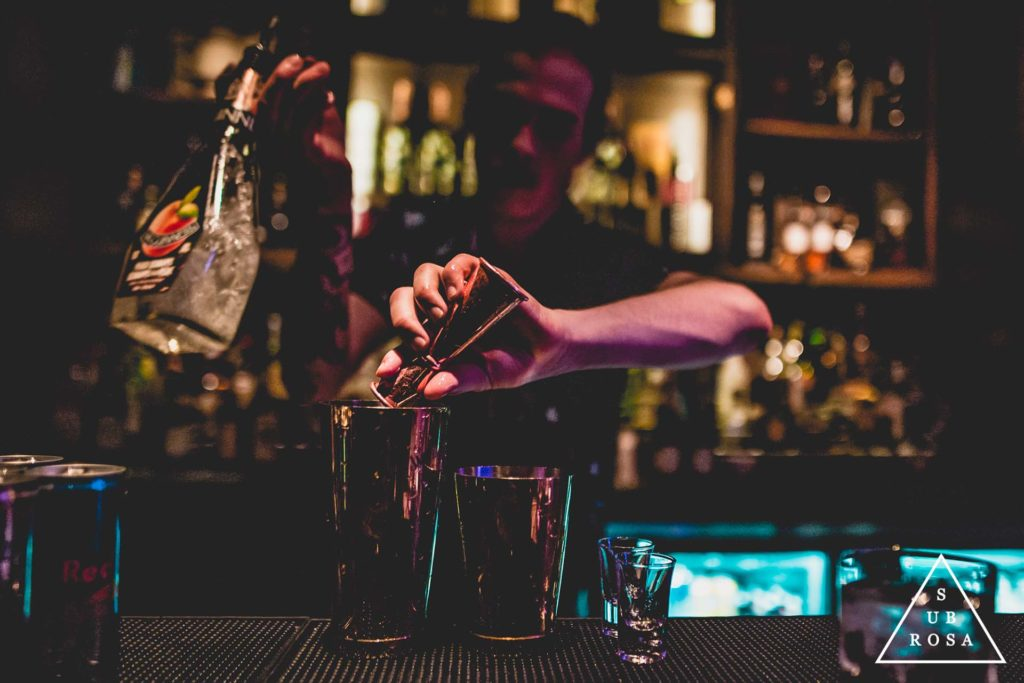 a bartender mixing craft cocktails in a dark underground speak-easy style lounge