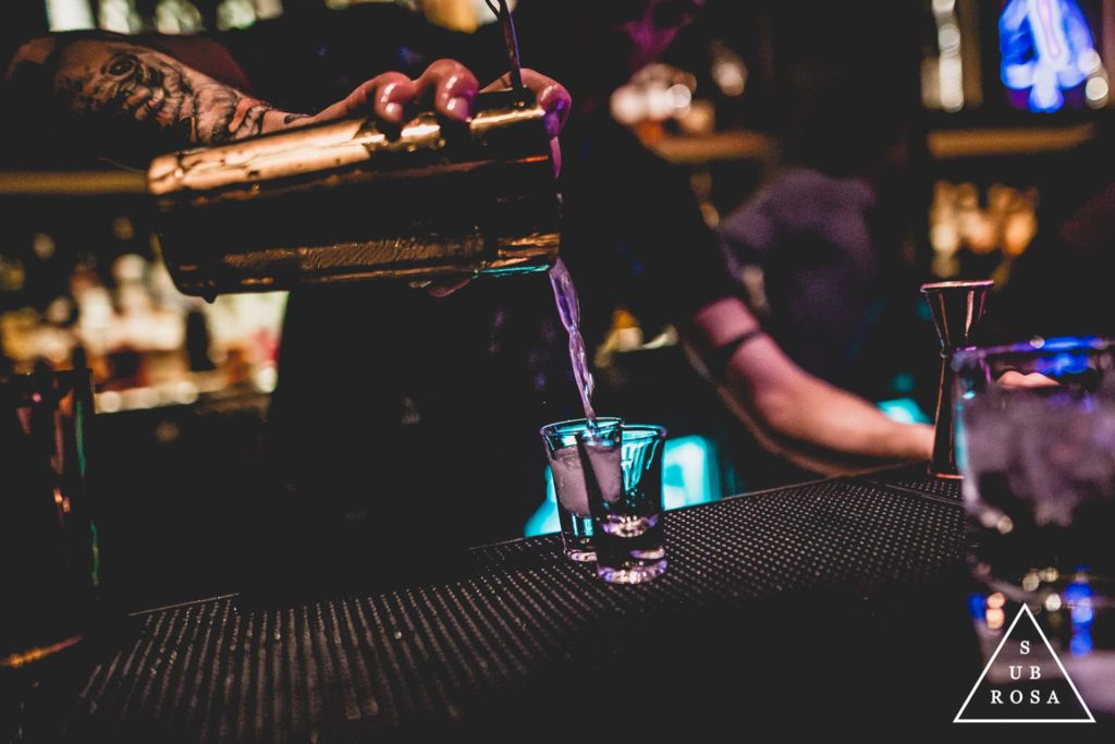a bartender pouring shots out of a strainer
