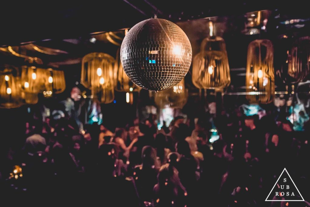 a disco ball hanging over a group of people in an underground lounge