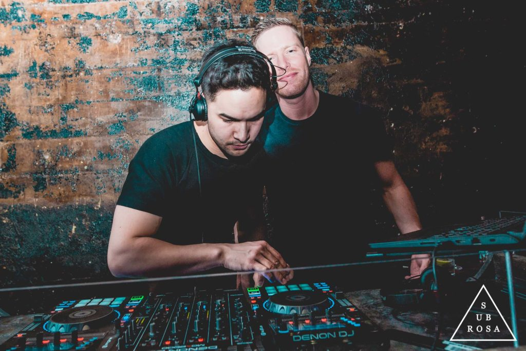 two DJs spinning music on electronic turntables in an underground lounge