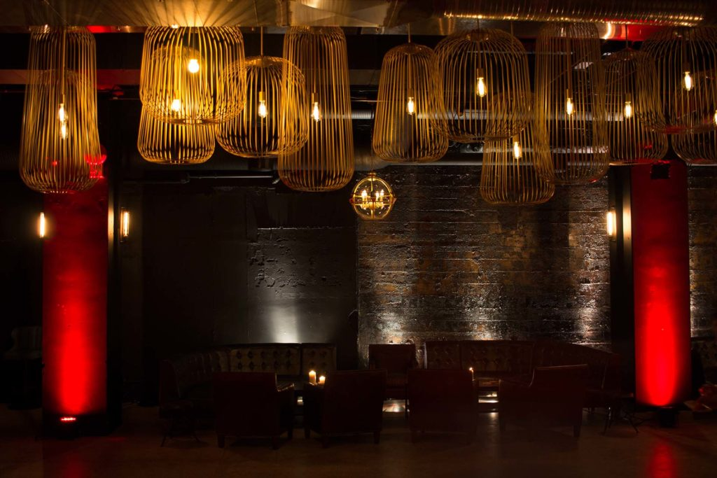 large filament bulbs, atmospheric red lights, and candles light a dark speak-easy style underground lounge