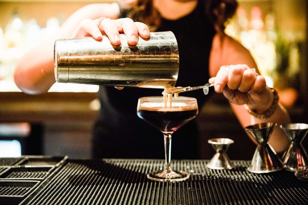 a bartender pouring a dark cocktail through a strainer into a glass