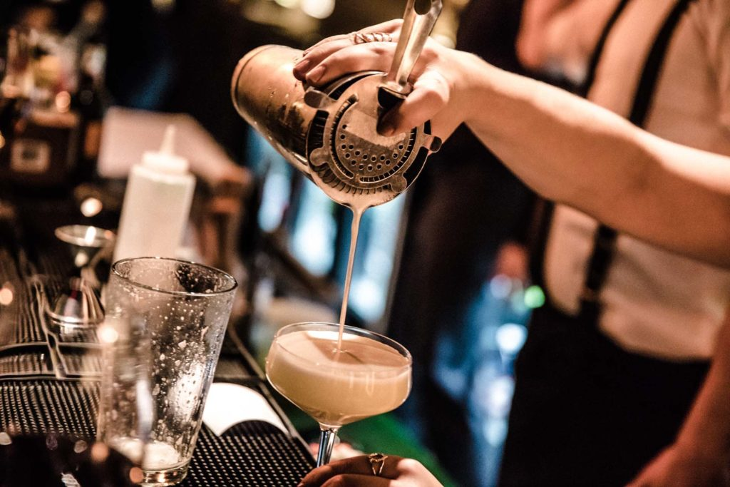 a bartender pouring a cocktail out of a shaker into a glass