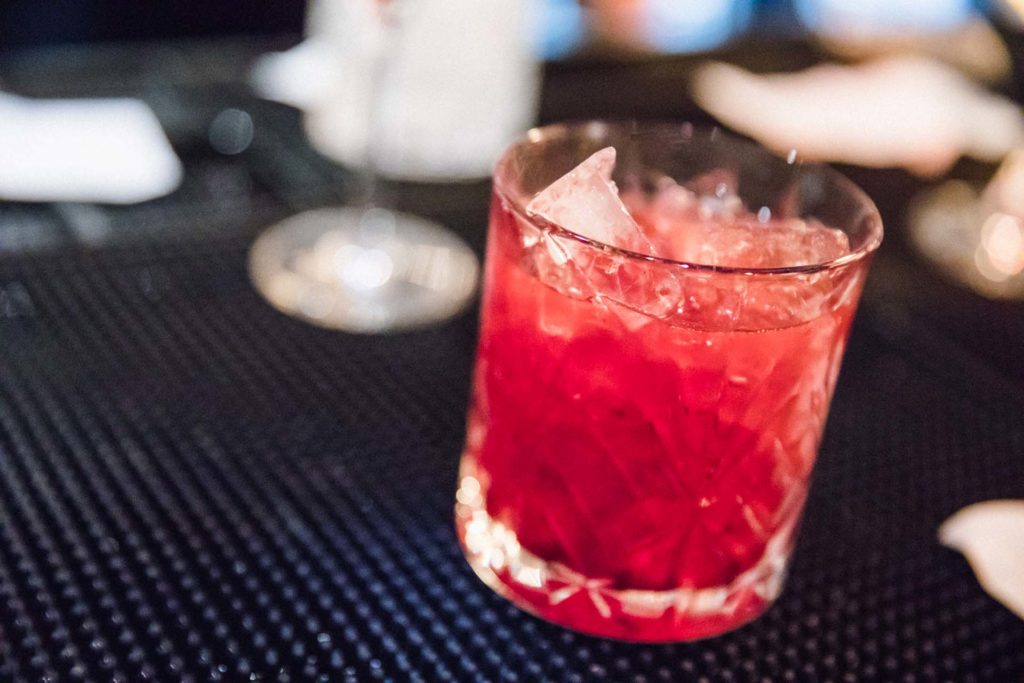 a red cocktail in a crystal rocks glass