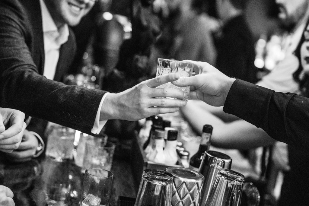 a bartender handing a man in a suit a cocktail in a crystal tumbler